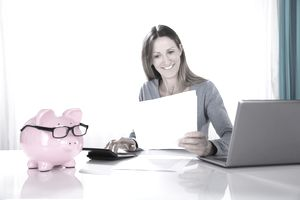 A woman smiling as she calculates finances