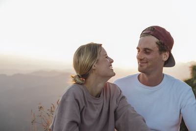 Happy young couple on a hiking trip having a break at sunrise