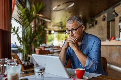 Contemplating businessman at laptop in a restaurant