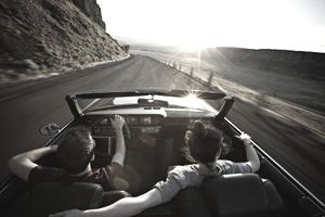 A Young Couple Driving Around a Bend in a Convertible
