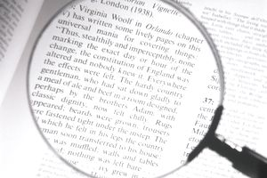 Magnifying glass enlarging the text on a page from a book