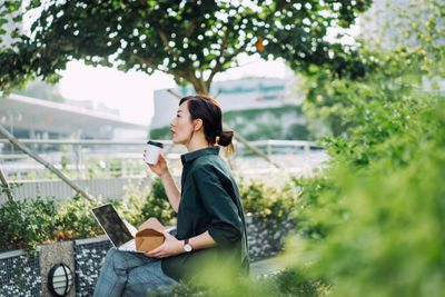 Woman working on a laptop and enjoying coffee sitting in a park