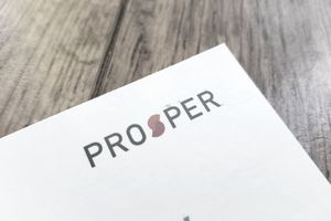 Paperwork from Prosper, a peer-to-peer lender, laying on a wooden desk.