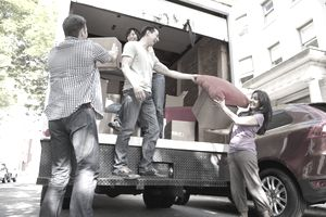 Young Adults moving stuff out of moving truck