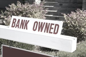 """A """"bank owned"""" sign in front of porch steps and shrubs"""