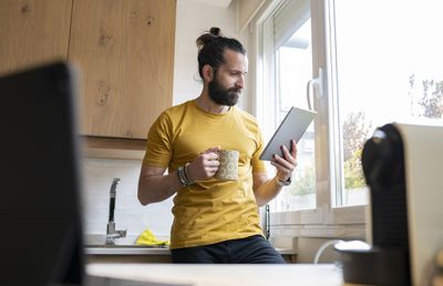Person holding coffee mug looks at digital tablet in kitchen