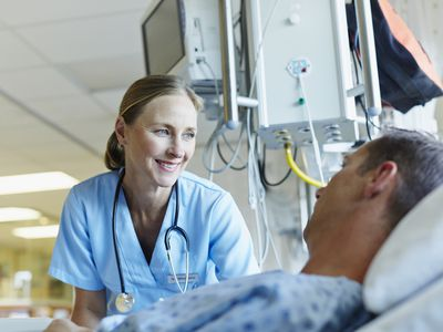 Smiling doctor looking at patient in hospital bed.