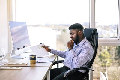 A man sits at his desk and determines the cash flow of a company he is considering investing in.