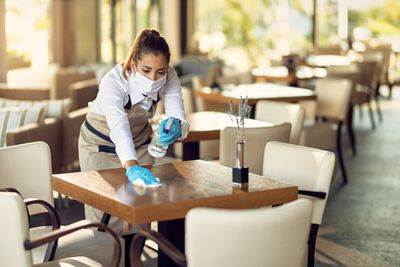 Waitress with a face mask and gloves cleaning tables with disinfectant in a cafe