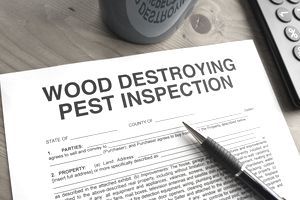 An uncompleted pest inspection form laying on a wooden table.