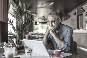 Man wearing spectacles sitting in a restaurant in front of his laptop