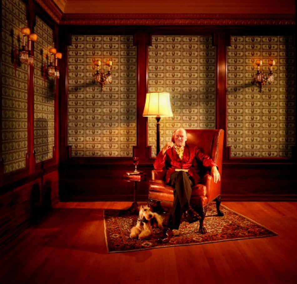 a man representing opulence sitting in an elegant room with wallpaper made of cash
