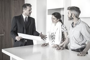 A real estate agent talks to couple at a counter.