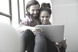 A couple sitting in a windowsill looks at a laptop