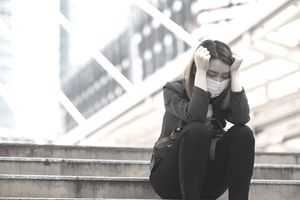 Unemployed woman sitting on stairs looking depressed - stock photo