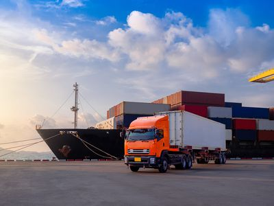 Loaded container ship in dock behind orange transport truck with white container loaded on it.