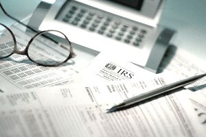 Calculator, pen, and eyeglasses set atop tax forms in preparation for filing taxes