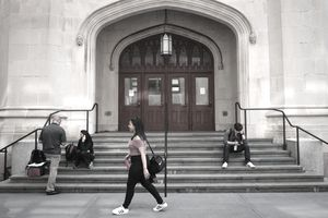 students walking past building entrance