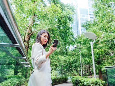 Young woman readers her cellphone in city park