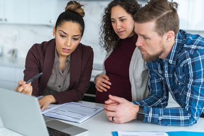 A young couple review their finances with a financial planner