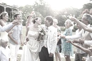 Guests throwing rose petals on bride and groom.