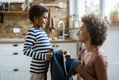 Single mother packing her small son for school.