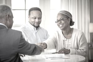 African American couple shaking hands with businessman