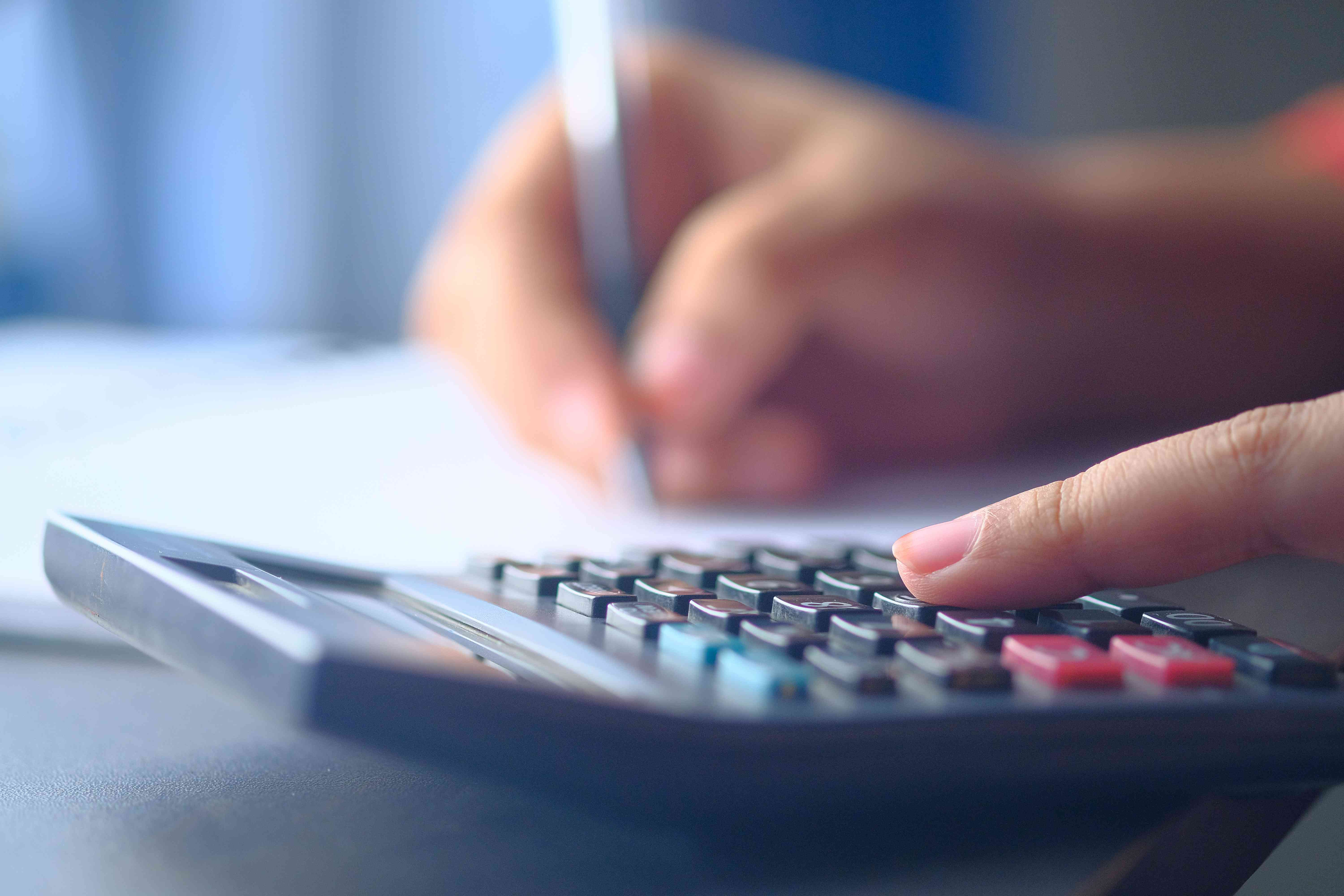 Woman tracking her spending by balancing her checkbook with a calculator