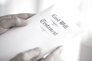 Hands holding a sheet of paper with Last Will and Testament written on it in a old style script.