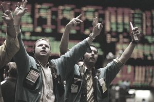 Stock traders waving arms on floor of stock exchange