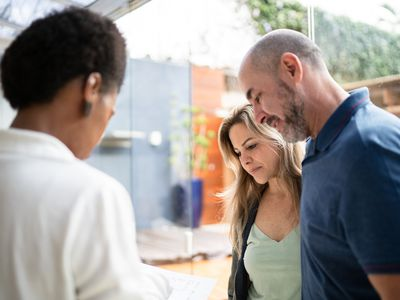 A real estate agent shows property to a couple.
