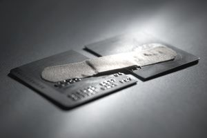 a broken credit card held together with a band-aid indicates a broken credit report status
