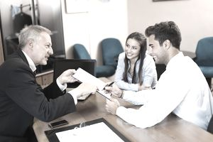 Young couple signing contract with man in suit
