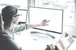 Woman pointing to two different computer screens with colorful stock charts on them.