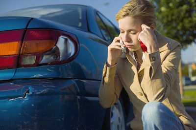 A driver crouches next to her car, which has a damaged bumper, while calling her insurer