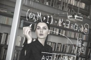 Woman writing math calculations on a clear glass board in an office
