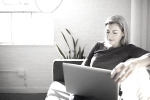 woman in black shirt with grey hair sitting on couch doing work