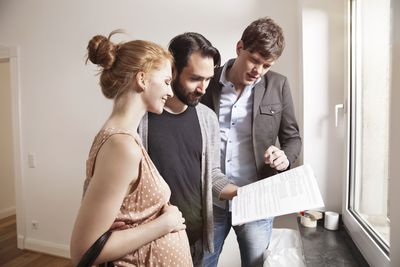 Real estate agent showing expecting parents a contract in a new apartment