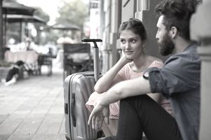 Couple Waiting at a Doorstep With Suitcases
