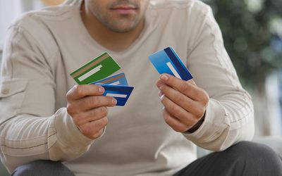 The pros and cons of credit cards man choosing between multiple credit cards reheart Images