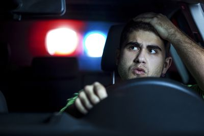 Man driving car being pulled over by police for driving without insurance.