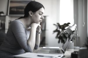 Worried young woman working on laptop at home