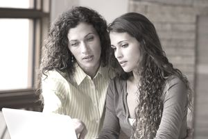 Mother and daughter standing close together reviewing college planning financials on a laptop
