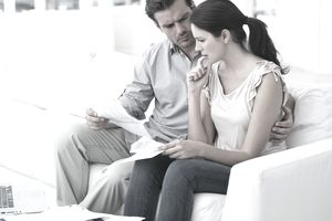 Worried couple reviewing papers in their home