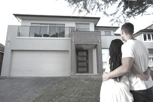 Couple outside their new bank-financed home with a loan that is now part of the secondary market.