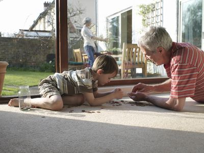 Grandfather and young grandson counting change on the floor