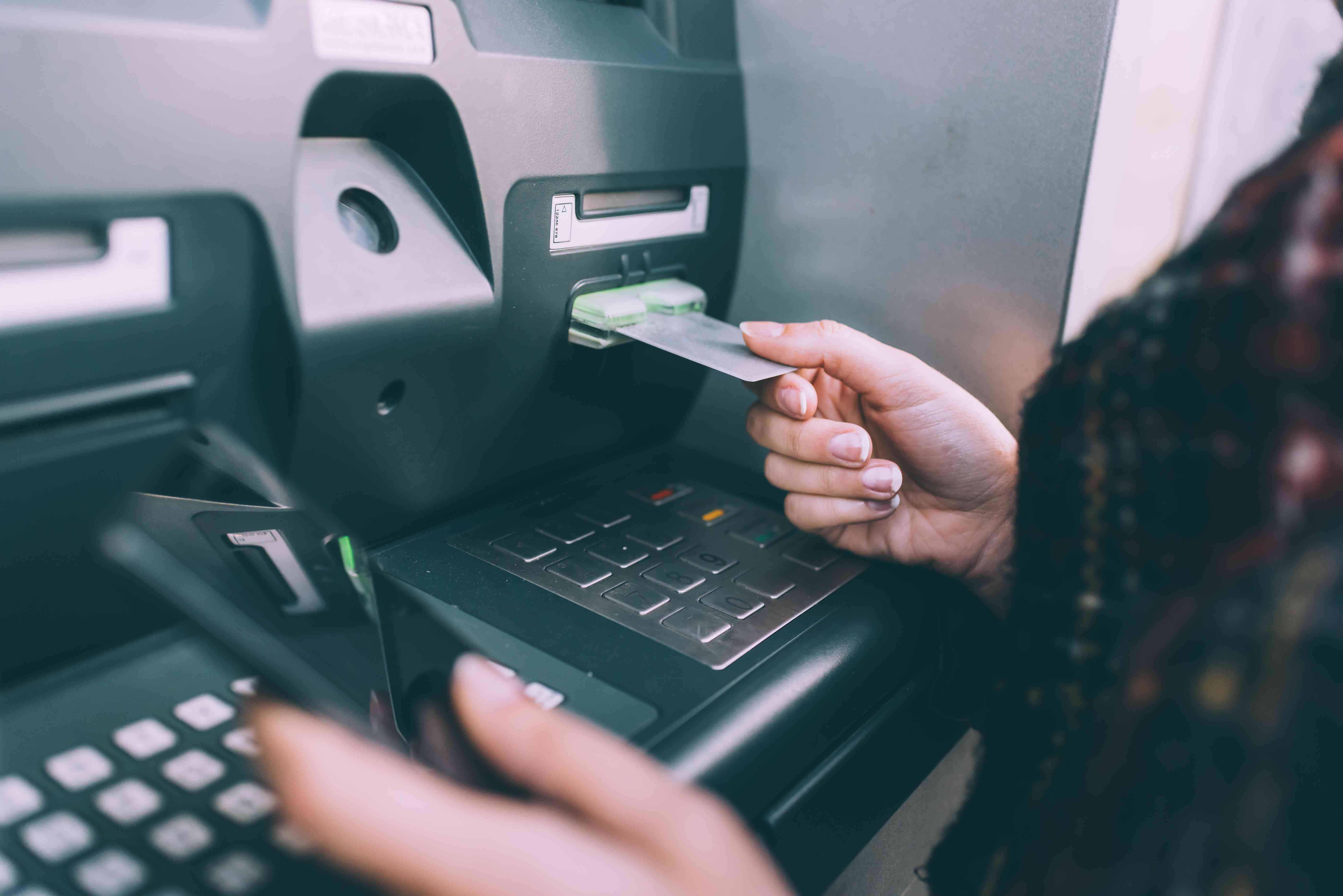 A woman using an ATM that will charge her account a fee