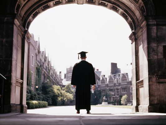 College graduate in cap and gown standing facing way in an archway at a university
