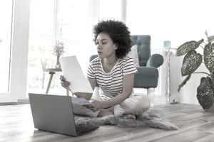 Young woman sitting on the floor by her laptop, looking through credit report