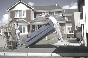 Young man lifting sofa standing on truck platform, woman watching standing by, side view